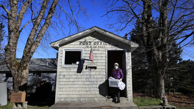 Postmistress Donna DeWitt carries mail at the tiny post office on Isle Au Haut, Maine. The post office serves the 70 or so year-round island residents.