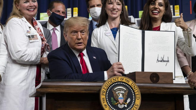 President Donald Trump holds up a signed executive order on lowering drug prices at a July 24 event in Washington.