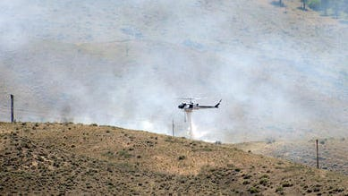 A Washoe County Sheriff's Office helicopter drops a load of water sucked from the nearby Steamboat Ditch on a wildfire Thursday afternoon in west Reno. The fire was located uphill from the Tom Cooke Trail intersection with the Steamboat Ditch Trail.