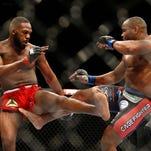 Jon Jones, left, exchanges kicks with Daniel Cormier, during their UFC light heavyweight title fight Jan. 3 in Las Vegas.