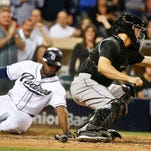 San Diego Padres' Justin Upton tags home plate while scoring in the Padres' eight run eighth inning as Colorado Rockies catcher Nick Hundley takes in a late throw in a baseball game Friday, May 1, 2015, in San Diego. The Padres won the game 14-3. (AP Photo/Lenny Ignelzi)