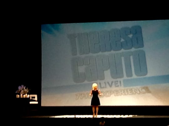 "Theresa Caputo stands on stage during her show, ""Theresa Caputo Live! The Experience."""