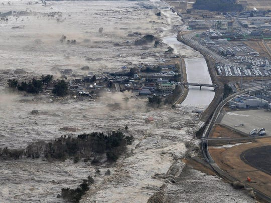 An earthquake-triggered tsunami sweeps shores along Iwanuma in northern Japan on Friday March 11, 2011.