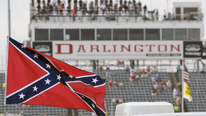 FILE - In this Sept. 5, 2015, file photo, a Confederate flag flies in the infield before a NASCAR Xfinity auto race at Darlington Raceway in Darlington, S.C. Bubba Wallace, the only African-American driver in the top tier of NASCAR, calls for a ban on the Confederate flag in the sport that is deeply rooted in the South. (AP Photo/Terry Renna, File) ORG XMIT: NY174