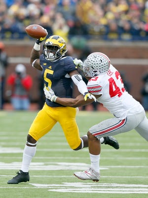 Michigan's Jabrill Peppers throws incomplete under pressure from Ohio State's Darron Lee in the first half of OSU's 42-13 win Nov. 28, 2015 in Ann Arbor.