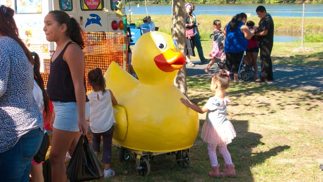 A young girl cuddles with a rubber ducky at the Raritan River Festival, which returns Sept. 24 to Boyd Park in New Brunswick. Highlights will include the Beez Foundation's annual Rubber Ducky Race to raise funds to combat brain cancer.