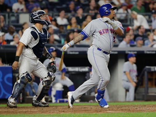New York Mets' Dominic Smith (22) follows through on a two-run home run as New York Yankees catcher Gary Sanchez watches during the seventh inning of a baseball game Tuesday, Aug. 15, 2017, in New York. (AP Photo/Frank Franklin II)