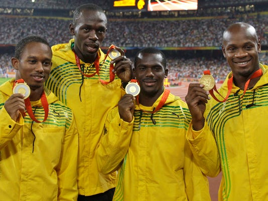 FILE - In this Saturday, Aug. 23, 2008 file photo, Jamaica's men's 4x100 meters relay team, from left, Michael Fraser, Usain Bolt, Nesta Carter and Asafa Powell show their gold medals during the athletics competitions in the National Stadium at the Beijing 2008 Olympics in Beijing. An appeal case involving the 2008 Olympic title stripped from Usain Bolt's Jamaica relay team is going to court in November 2017. (AP Photo/Petr David Josek, File)