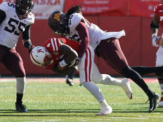 Minnesota Golden Gophers defender De'Vondre Campbell (26) tackles Nebraska Cornhuskers quarterback Tommy Armstrong Jr. (4) in the second half at Memorial Stadium. Minnesota won 28-24. Mandatory Credit: Bruce Thorson-USA TODAY Sports