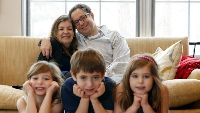 Charlie Breslin, background right, sits with his wife Nancy and their three children, from left, Kate, 6, Alan, 9, and Lila, 6, in their home in Glen Ridge, N.J.