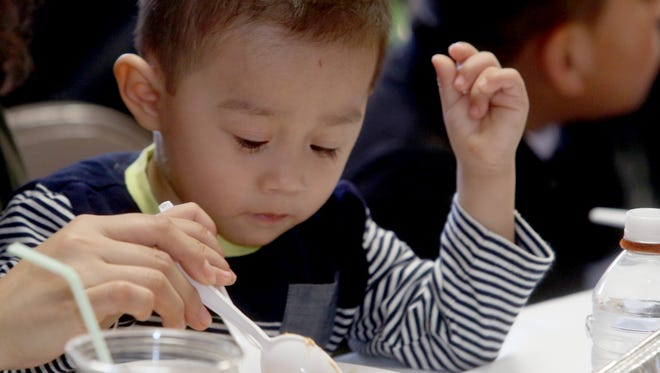 Yeshua Deciderio, 2, of Mount Kisco, eats his Christmas dinner during the 23rd annual Westchester Christmas Dinner at St. Mary's School in Katonah Dec. 25, 2016. About 300 volunteers served Christmas dinner, handed out donated toys and clothes, and provided entertainment for over 300 members of the community from all over Westchester County.