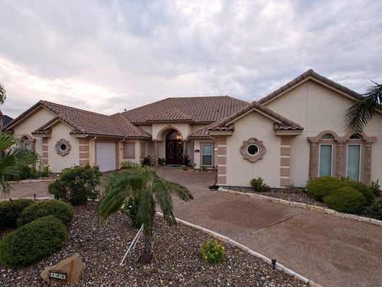 The attractive stucco and red tile roofed home sits