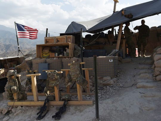 U.S. soldiers from NATO look on as U.S. flag flies