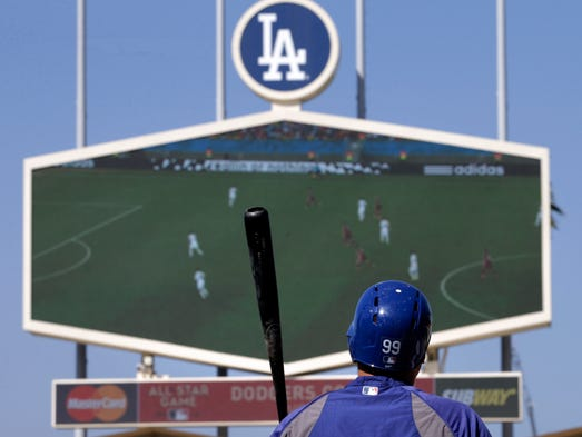 Los Angeles Dodgers starting pitcher Hyun-Jin Ryu of South Korea watches a World Cup soccer match between Russia and South Korea while taking batting practice before the team's baseball game against the Colorado Rockies on Tuesday, June 17, 2014, in Los Angeles.