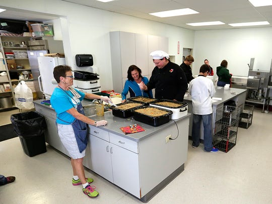 Val Lenz works with students at Broken Bread, in St