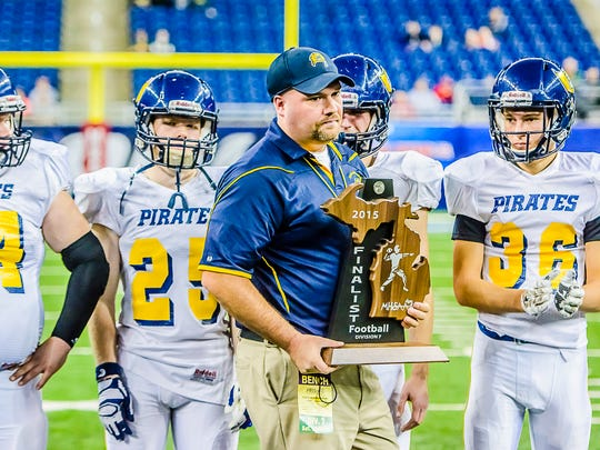 Pewamo-Westphalia Head Football Coach Jeremy Miller holds the state runner-up trophy after the Pirates' loss in the Division 7 State Championship game to Ishpeming Saturday at Ford Field in Detroit.