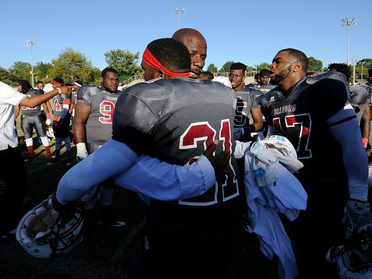 Lane College head coach Derrick Burroughs hugs defensive back JustinÊHill (21) after the Dragons defeated Benedict College 19-18 at Lane Field in Jackson, Tenn., on Saturday, Oct. 8, 2016.