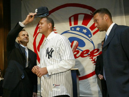 Yankees manager Joe Torre puts a cap on the newest