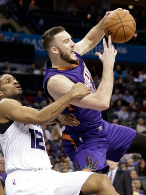 Charlotte Hornets' Gary Neal, left, fouls Phoenix Suns' Miles Plumlee during the second half of an NBA basketball game in Charlotte, N.C., Wednesday, Dec. 17, 2014. The Suns won 111-106.