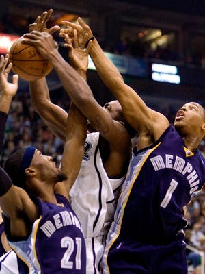 Utah Jazz forward Paul Millsap battles with Memphis Grizzlies forward Hakim Warrick (21) and guard Kyle Lowry (1) for a rebound during the second quarter of an NBA basketball game Wednesday, Nov. 26, 2008, in Salt Lake City. (AP Photo/Douglas C. Pizac)