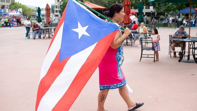 Ivonne Martinez of Worcester carries around a large Puerto Rican flag during last year's Latin American Festival on Worcester Common. Organizers decided to cancel the festival this year because of concerns over the coronavirus.