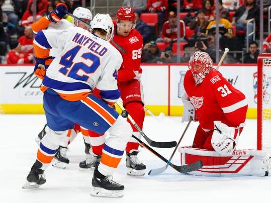 Detroit Red Wings goaltender Jared Coreau (31) stops a New York Islanders defenseman Scott Mayfield (42) shot in the first period of an NHL hockey game Saturday, April 7, 2018, in Detroit. (AP Photo/Paul Sancya)