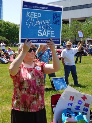 A woman holds a sign aloft during an April 25 demonstration in Raleigh  in favor of HB2.