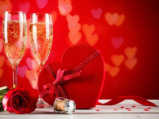A table has champagne glasses, a box of heart-shaped chocolates, and a rose.