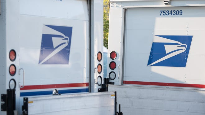 Postal trucks are parked at a United States Postal Service post office location in Washington, DC.