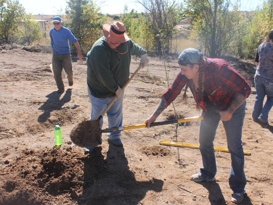 Andy Broyles and Belen Hunt dig a hole to plant a orchard