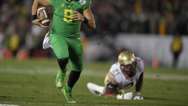 Jan 1, 2015; Pasadena, CA, USA; Oregon Ducks quarterback Marcus Mariota (8) scores on a 23-yard touchdown run in the fourth quarter against the Florida State Seminoles in the 2015 Rose Bowl college football game at Rose Bowl. Oregoon defeated Florida State 59-20. Mandatory Credit: Kirby Lee-USA TODAY Sports
