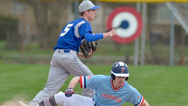 Salem's Gage Moyers (5) turns a double play Monday, while Livonia Frankin's Kolby Dewhirst (17) is out at second base.