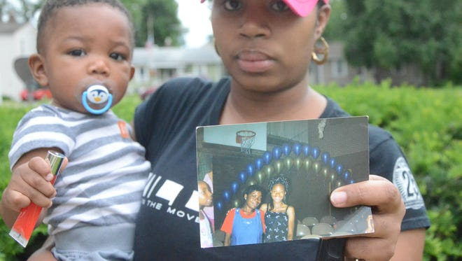 Cherrelle Haney-Jones holds her son, Ra'jah Jones, 1, and a photograph of her aunt (red shirt), Liza Haney-Nelson.