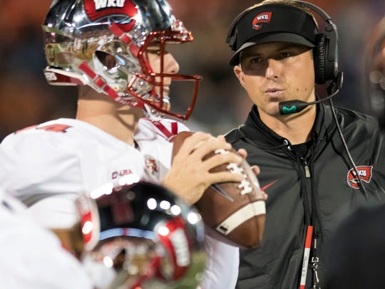 Western Kentucky coach Mike Sanford, right, talks to