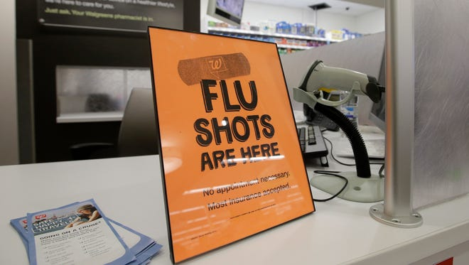 A sign lets customers know they can get a flu shot in a Walgreen store. Local school districts are seeing a rise in absences due to illness.