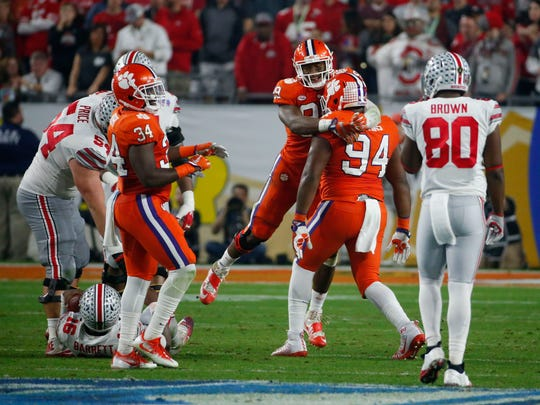 The Clemson defense celebrates a sack on Ohio State Buckeyes quarterback J.T. Barrett (16) during the second quarter of the College Football Playoff Semifinal game in the PlayStation Fiesta Bowl on Dec. 31, 2016 at University of Phoenix Stadium in Glendale, Arizona.