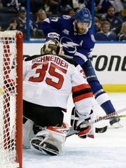 New Jersey Devils goaltender Cory Schneider (35) stops a shot by Tampa Bay Lightning defenseman Victor Hedman (77) during the second period of Game 5 of an NHL first-round hockey playoff series Saturday, April 21, 2018, in Tampa, Fla.