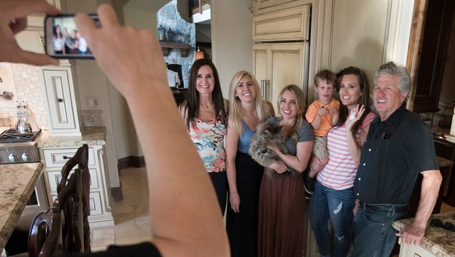 Laurie Force (left), Courtney Force, Brittany Force, Ashley Force Hood holding son Jacob, Daniel Hood (partial hidden) and John Force shoot a video for social media in the kitchen of John and Laurie's home.
