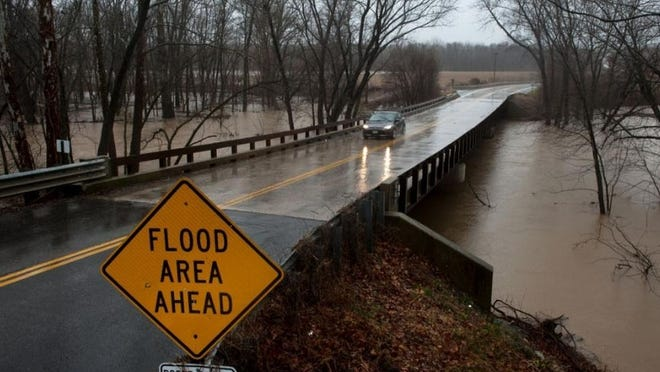 FILE- A vehicle passes over a swollen Perche Creek on Gillespie Bridge Road in December 2015.