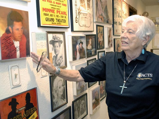 Barbara Hubbard points to one of several signed photos of famous country music acts, including this one of Vince Gill, in her home.