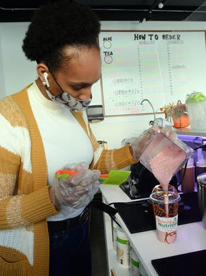Dilma DePina of Norwich makes a strawberry banana shake at her new store, Norwich Nutrition, at 27 Broadway in downtown Norwich Thursday.