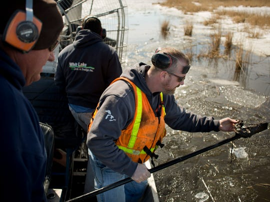 Contractor Jeremy Bernhardt inspects the depth and