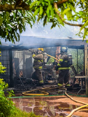 Guam Fire Department personnel combine their efforts to eliminate smoldering hotspots after responding to a housefire on North Ukudo Street in Dededo on Tuesday, Dec. 26, 2017. The structure was fully engulfed in flames when firefighters initially arrived at the scene, according to Cherika Chargualaf, GFD acting spokeswoman. Thankfully, none of the four adults liviing in the three-bedroom wood and tin home were injured by the blaze, said occupant Jacob De Guzman, 19.