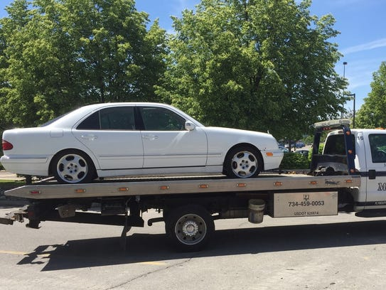 A bomb-threat suspect's Mercedes is towed from the