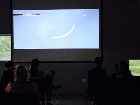 Eclipse watchers at Cranbrook Science Center watch a NASA livestream as clouds roll in outside, obscuring the eclipse.