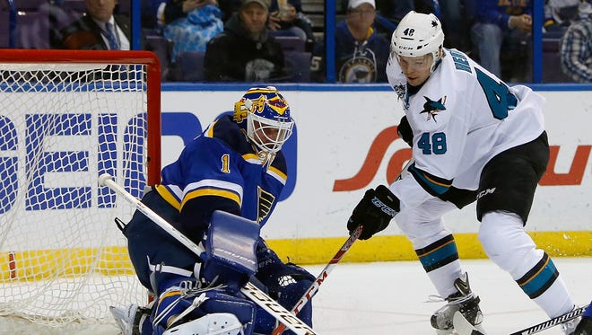 San Jose Sharks' Tomas Hertl, right, of the Czech Republic, gets the puck past St. Louis Blues goalie Brian Elliott  to score a goal during the first period.