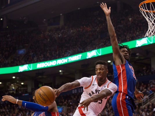 Toronto Raptors' Delon Wright, center, passes the ball as Detroit Pistons' Andre Drummond, left, and Reggie Bullock, right, defend during first-half NBA basketball game action in Toronto, Monday, Feb. 26, 2018. (Chris Young/The Canadian Press via AP)