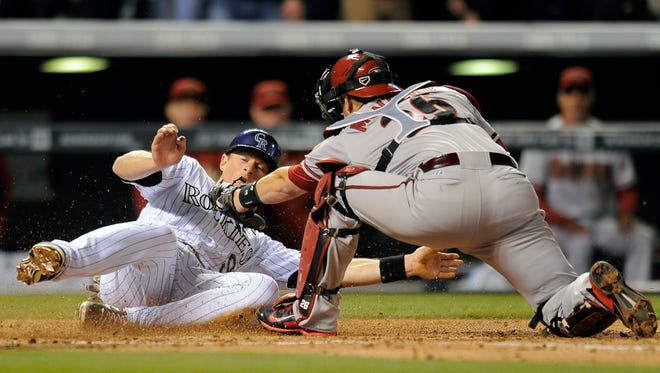 Colorado Rockies DJ LeMahieu, left, slides safely past the tag by Diamondbacks catcher Miguel Montero, right, to score in the fifth inning of a baseball game Saturday, April 5, 2014, in Denver.