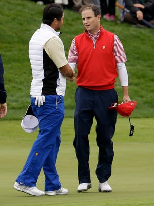 Zach Johnson is congratulated by International team player Jason Day after winning their singles match at the Presidents Cup.