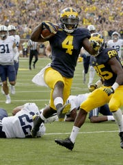 Michigan's De'Veon Smith high-steps into the end zone to finish off a 60-yard TD against Brigham Young on Sept. 26, 2015, at Michigan Stadium.